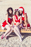 Amigos felices en los sombreros de santa en la playa Vacaciones de la Navidad Imagen de archivo