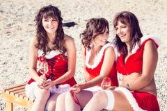 Amigos felices en los sombreros de santa en la playa Vacaciones de la Navidad Imagen de archivo libre de regalías