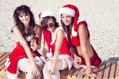 Amigos felices en los sombreros de santa en la playa Vacaciones de la Navidad Fotos de archivo libres de regalías