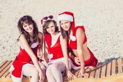 Amigos felices en los sombreros de santa en la playa Vacaciones de la Navidad Imágenes de archivo libres de regalías