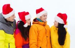 Amigos felices en los sombreros de santa y los trajes de esquí al aire libre Foto de archivo