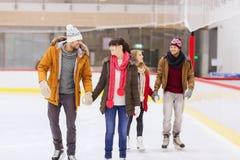 Amigos felices en pista de patinaje Imagen de archivo libre de regalías