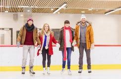 Amigos felices en pista de patinaje Fotos de archivo