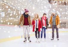 Amigos felices en pista de patinaje Imagenes de archivo