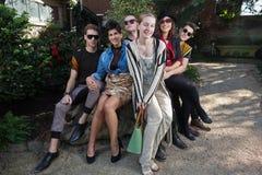 Amigos felices en roca en parque Imagen de archivo libre de regalías