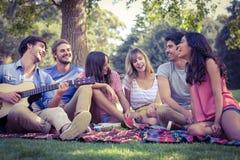 amigos felices en un parque que tiene una comida campestre Imagen de archivo libre de regalías