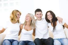 Amigos felices en un sofá Imagenes de archivo