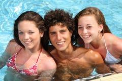 amigos felices en una piscina Imágenes de archivo libres de regalías