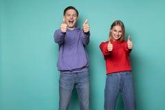 Amigos felices hermosos muchacho y muchacha en la ropa casual que muestra los pulgares para arriba y que mira la c?mara foto de archivo libre de regalías