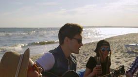 Amigos felices jovenes que beben la cerveza, sentándose en easychairs en la playa y escuchando un amigo que toca la guitarra en a almacen de video