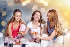 Amigos felices o muchachas adolescentes que comen la pizza en casa Imagen de archivo