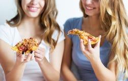 Amigos felices o muchachas adolescentes que comen la pizza en casa Fotografía de archivo