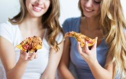 Amigos felices o muchachas adolescentes que comen la pizza en casa Fotos de archivo