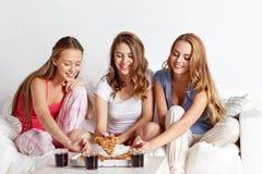 Amigos felices o muchachas adolescentes que comen la pizza en casa Foto de archivo