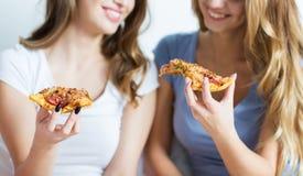 Amigos felices o muchachas adolescentes que comen la pizza en casa Foto de archivo libre de regalías