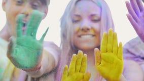 Amigos felices que agitan las manos pintadas en el polvo colorido, gesticulando hola, partido metrajes
