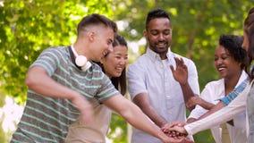 Amigos felices que apilan las manos en parque del verano metrajes