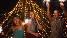 Amigos felices que bailan con las bengalas en el partido de la noche metrajes
