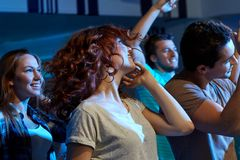 Amigos felices que bailan en el club de noche Foto de archivo