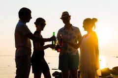 Amigos felices que beben bebidas y que tienen un partido Fotos de archivo libres de regalías