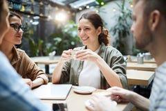 Amigos felices que beben el café en café fotografía de archivo libre de regalías