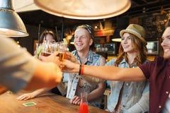 Amigos felices que beben la cerveza en la barra o el pub Fotografía de archivo