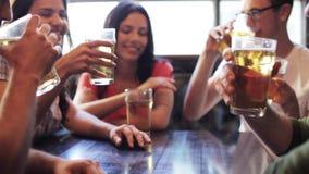Amigos felices que beben la cerveza en la barra o el pub almacen de video