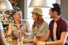 Amigos felices que beben la cerveza y los cócteles en la barra Foto de archivo libre de regalías