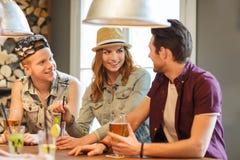 Amigos felices que beben la cerveza y los cócteles en la barra Foto de archivo