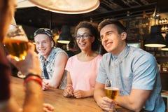 Amigos felices que beben la cerveza y que hablan en la barra Fotografía de archivo libre de regalías