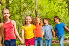 Amigos felices que caminan junto en el parque del verano Foto de archivo