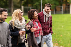 Amigos felices que caminan a lo largo de parque del otoño Foto de archivo