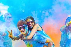 Amigos felices que celebran festival feliz del día de fiesta del holi foto de archivo