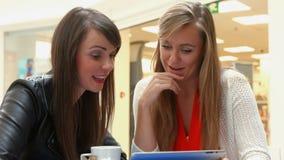 Amigos felices que comen café junto usando la tableta metrajes