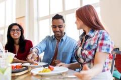Amigos felices que comen en el restaurante imagen de archivo