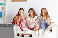 Amigos felices que comen la pizza y que ven la TV en casa Imágenes de archivo libres de regalías