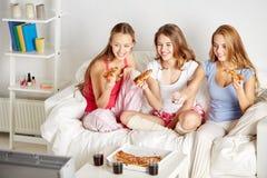 Amigos felices que comen la pizza y que ven la TV en casa Imagen de archivo
