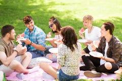 Amigos felices que comen la sandía en la comida campestre del verano Fotografía de archivo libre de regalías