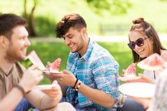 Amigos felices que comen la sandía en la comida campestre del verano Imagen de archivo libre de regalías