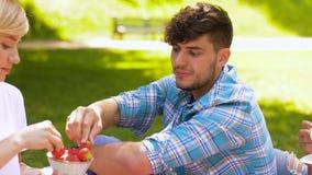 Amigos felices que comen las fresas en la comida campestre del verano almacen de metraje de vídeo