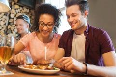 Amigos felices que comen y que beben en la barra o el pub Foto de archivo libre de regalías