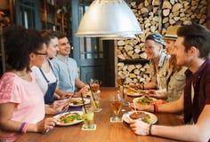Amigos felices que comen y que beben en la barra o el pub Foto de archivo