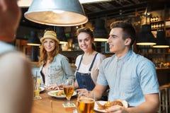 Amigos felices que comen y que beben en la barra o el pub Fotografía de archivo