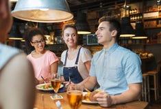 Amigos felices que comen y que beben en la barra o el pub Imagen de archivo libre de regalías