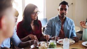 Amigos felices que comen y que hablan en el restaurante metrajes