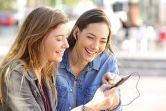 Amigos felices que comparten música en línea Imágenes de archivo libres de regalías