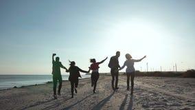 Amigos felices que corren en línea de la playa