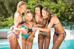 Amigos felices que gozan en la piscina Imagenes de archivo