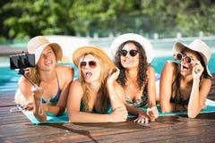 Amigos felices que gozan en la piscina Fotos de archivo