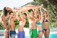 Amigos felices que gozan en la piscina Imágenes de archivo libres de regalías